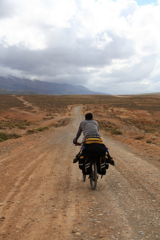 Morocco, Cirque du Jaffar. Cyclist on the road from Midelt