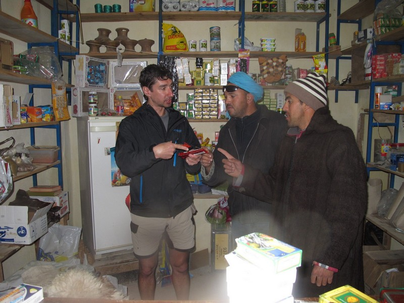 Morocco, Tagoudite. Buying food in rural shop boutique