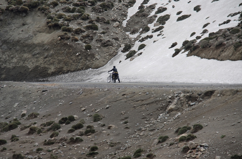 Morocco, High Atlas. Cyclist near snow pass