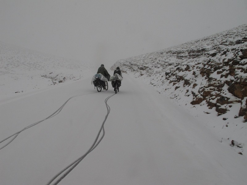 Morocco, High Atlas. Two cyclists under snow.