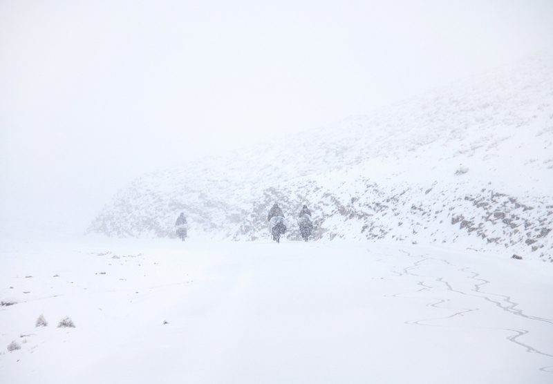 Morocco, High Atlas. Three cyclists run up to the mountain under snow