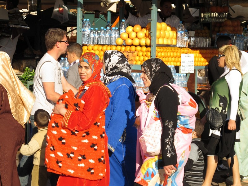 Morocco, Marrakesh. Women and children with fresh juice on background