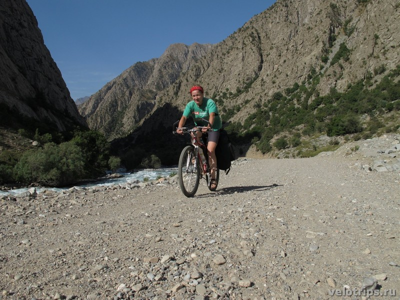 Tajikistan, Rufigar. Woman on bicycle on road