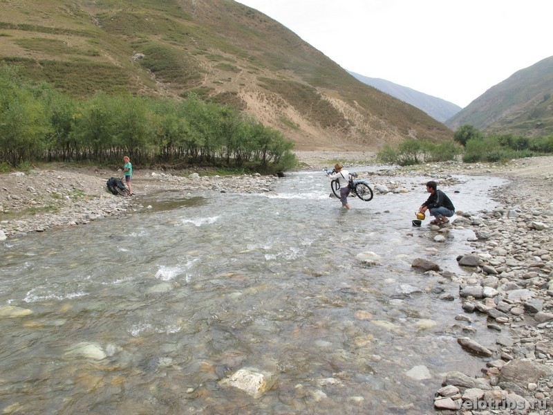 Tajikistan, Rufigar. River wade with bicycle