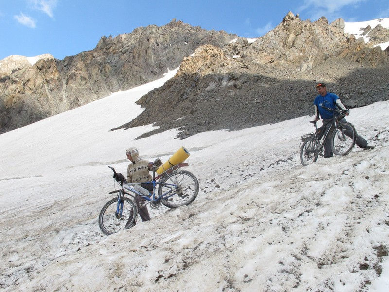 Tajikistan, Rost pass. Haul bicycles through glaciers snow